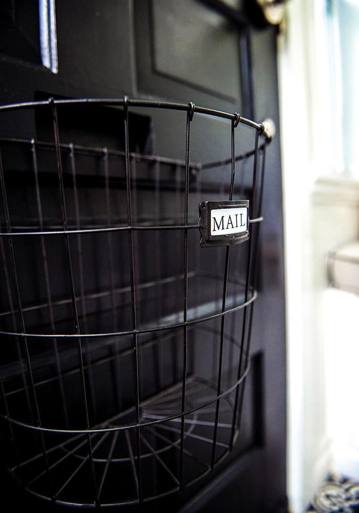Black wire mailbox on a heritage door